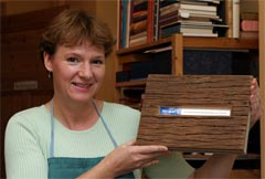 Christine Merkel-Köppchen shows a hand-crafted book cover made of wood